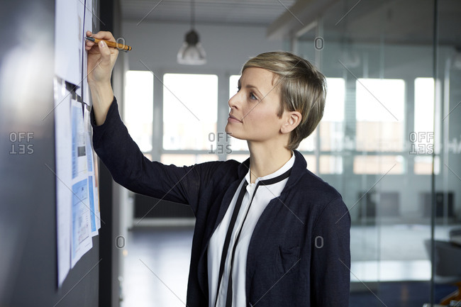 Businesswoman writing on paper at the wall in office