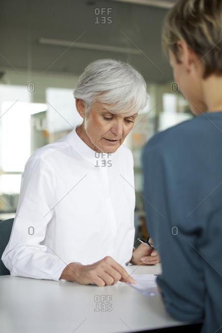 Two businesswomen talking at desk in office
