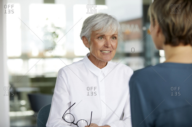 Portrait of senior businesswoman talking to colleague in office