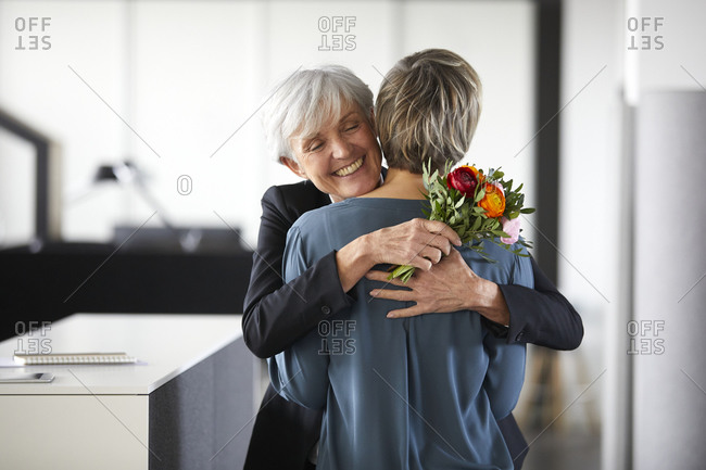 Happy senior businesswoman with bunch of flowers hugging colleague in office