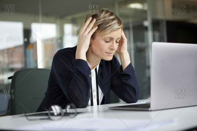 Businesswoman in office with head in hands and closed eyes