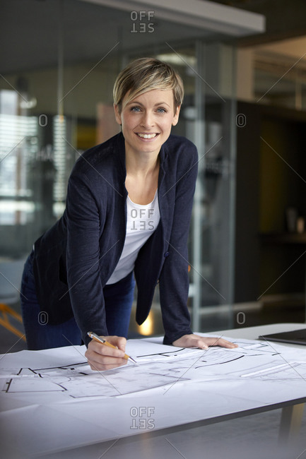 Portrait of smiling woman working on construction plan in office