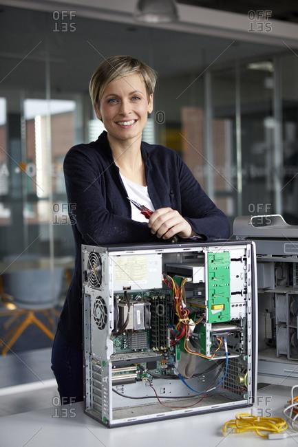 Portrait of smiling woman assembling desktop pc in office