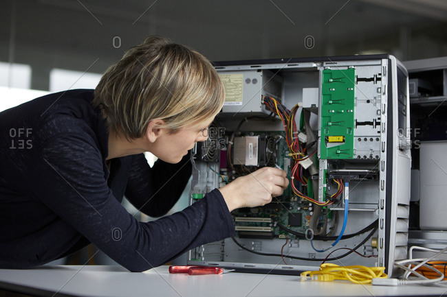 Woman assembling desktop pc in office