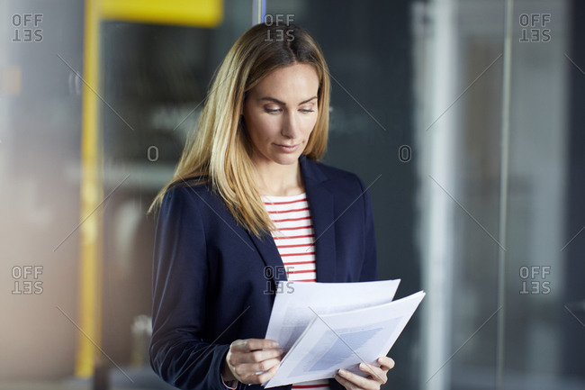 Portrait of businesswoman reviewing papers in office