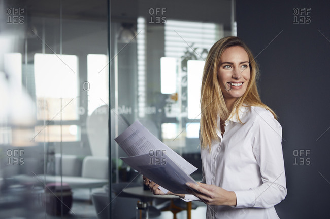 Smiling businesswoman holding papers in office