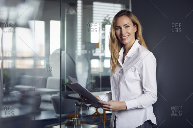 Portrait of confident businesswoman holding papers in office