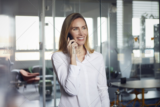 Portrait of smiling businesswoman on the phone in office