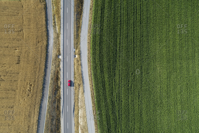 Germany- Bavaria- Drone view of country road cutting through green and yellow countryside fields in summer