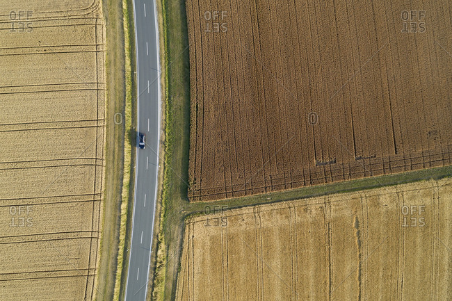 Germany- Bavaria- Drone view of country road cutting through brown and yellow countryside fields in summer