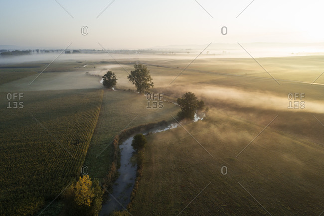 Germany- Bavaria- Drone view of river Aisch and surrounding countryside landscape at foggy sunrise