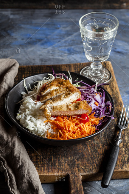Bowl of ready-to-eat salad with white and red cabbage- carrots- rice and chicken schnitzel