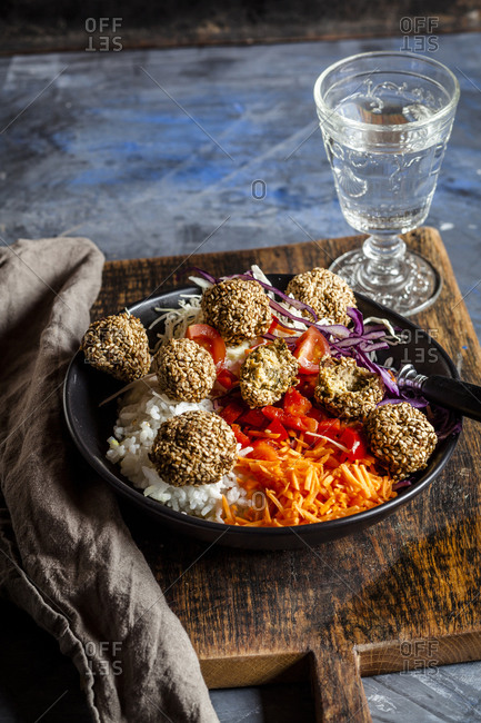 Bowl of ready-to-eat salad with white and red cabbage- carrots- rice and spinach falafel
