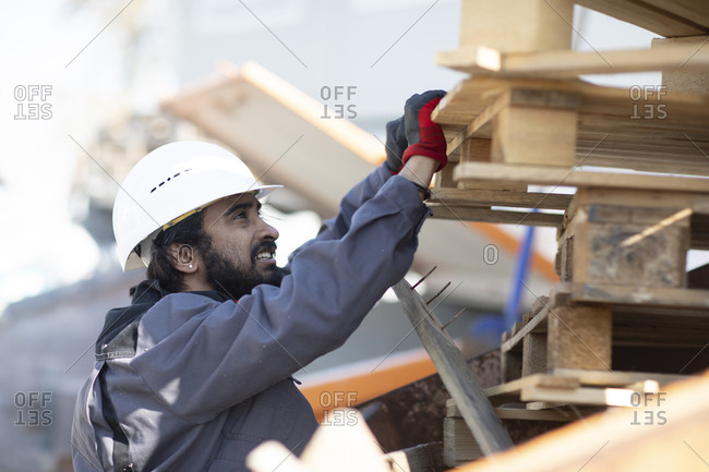 Technician wearing helmet and beard checking wooden paletts