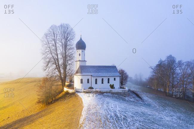 Germany- Bavaria- Bad Heilbrunn- Drone view of Kirche Maria Heimsuchung at foggy winter dawn
