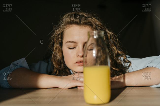 Portrait of blond young woman with closed eyes leaning on tabletop