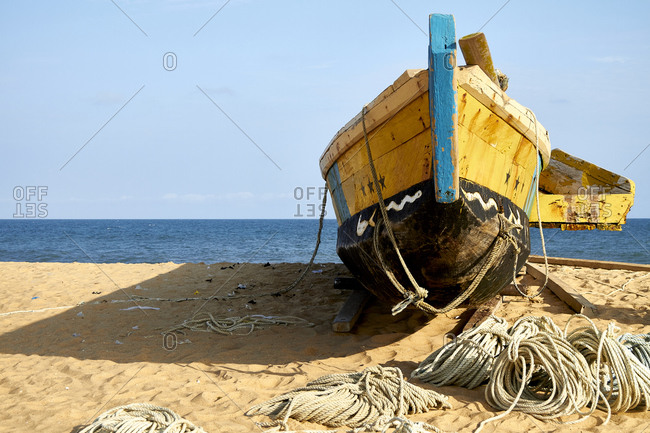 Ghana- Keta- Old fishing boat left on sandy coastal beach