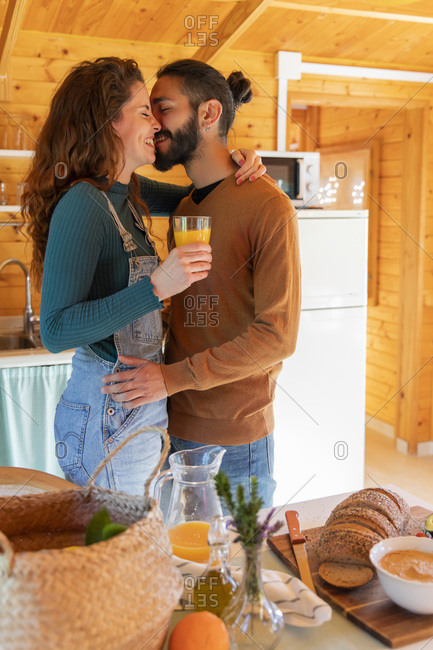 Happy young couple cuddling in a wooden cabin