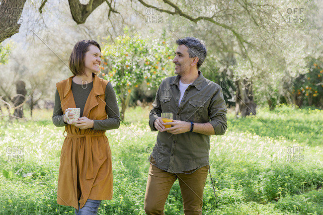 Happy couple with coffee and orange juice in the countryside