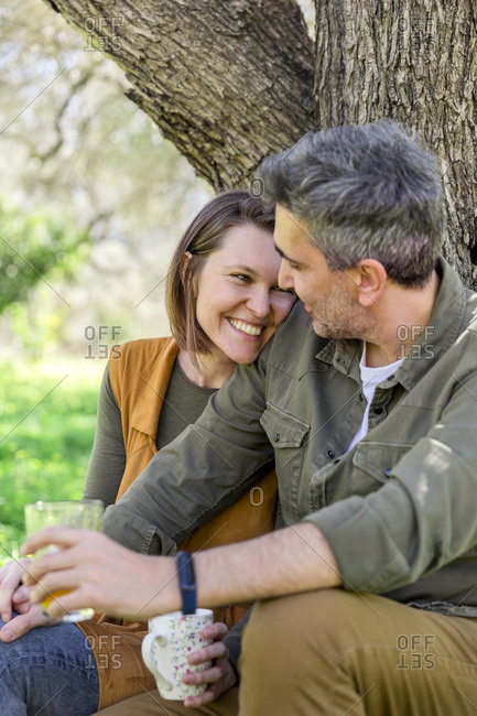 Happy couple sitting at a tree in the countryside