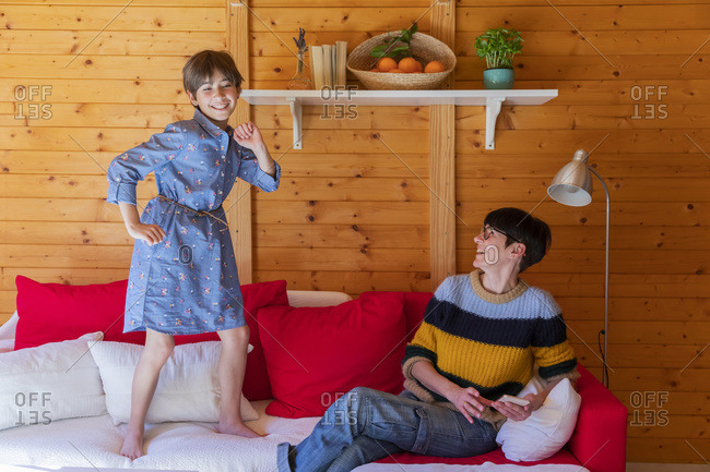 Happy mother and daughter on couch in a wooden cabin