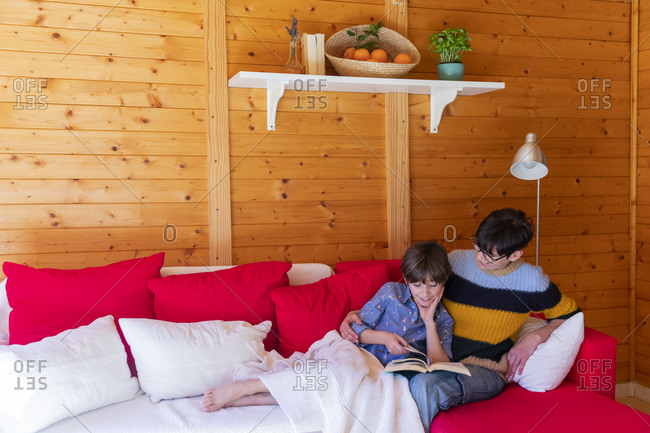 Mother and daughter reading a book on couch in a wooden cabin