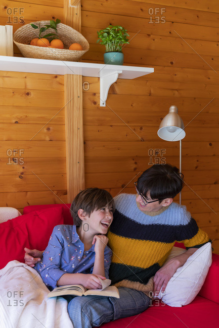 Happy mother and daughter reading a book on couch in a wooden cabin