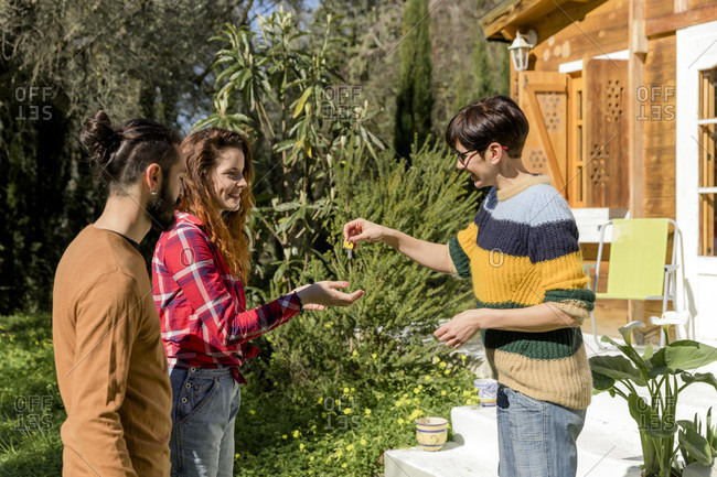 Host welcoming young couple outside a cabin in the countryside handing over house key