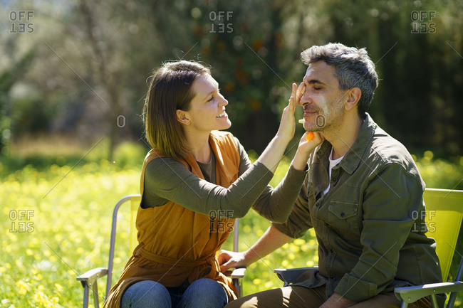 Young woman putting sunscreen on her boyfriend in the field
