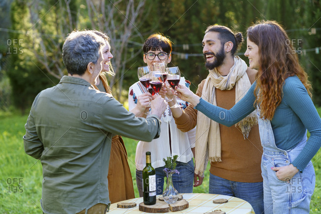 Group of friends toasting with red wine on their getaway in the countryside