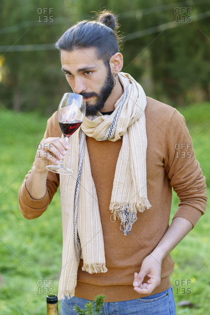 Portrait of young man tasting red wine in the countryside