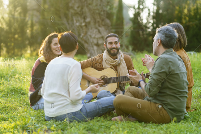 Group of friends playing music with the guitar sitting on the grass in the field