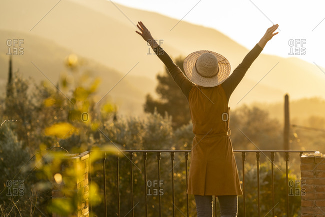 Woman enjoying the view of the sunset in the countryside raising arms- Orgiva- Andalusia- Spain