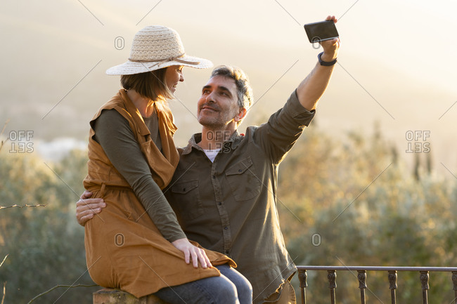 Couple taking selfie with smartphone during the sunset in the countryside