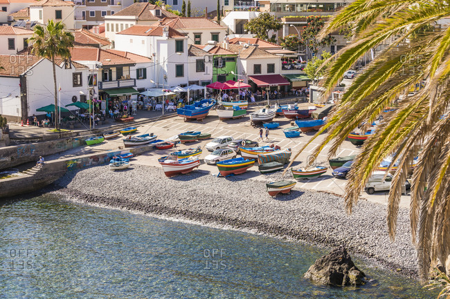 May 25, 2019: Portugal- Madeira- Camara de Lobos- Boats left on beach of coastal town in summer