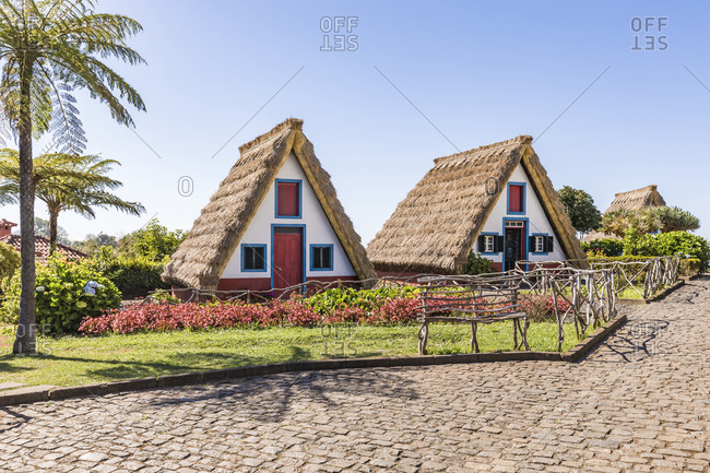 Portugal- Madeira- Santana- Cobblestone in front of traditional triangle shaped town house with thatched roof