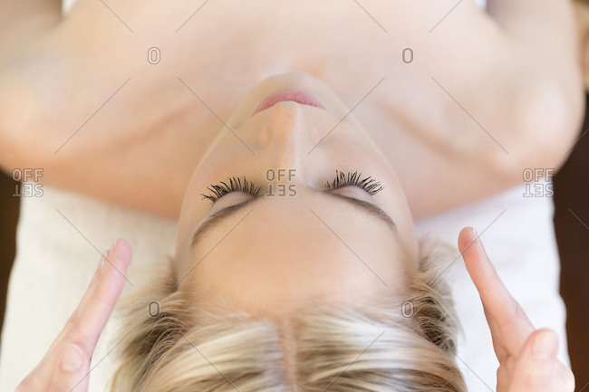Woman getting head massage during spa treatment