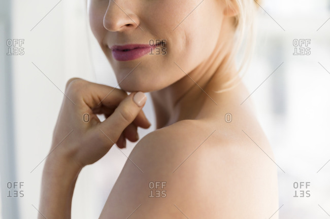 Close up of woman's smile and bare shoulder