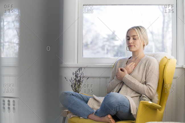Woman peacefully meditating at home