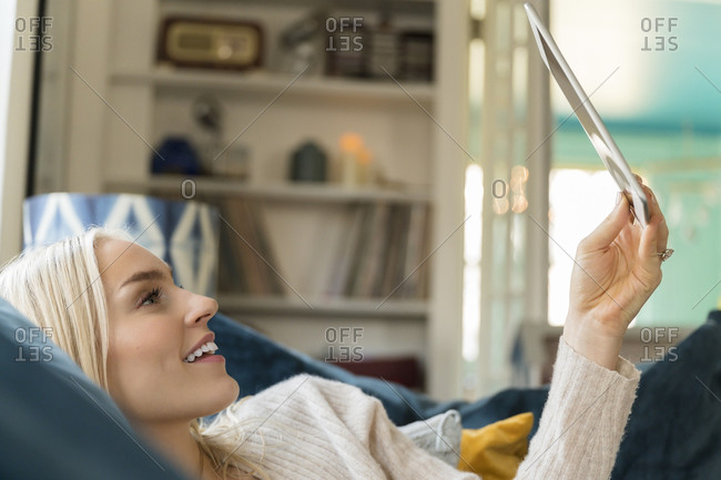 Woman using tablet while lying on sofa
