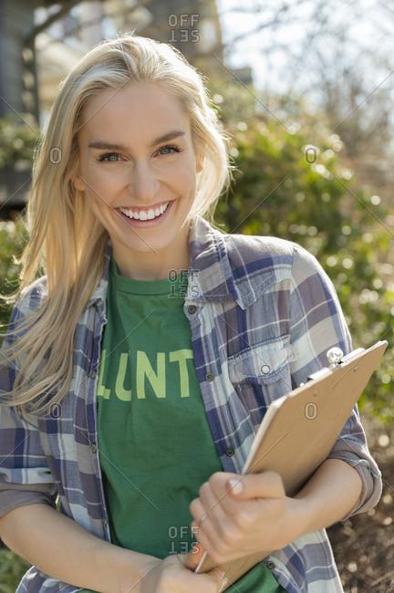 Smiling female volunteer holding clipboard