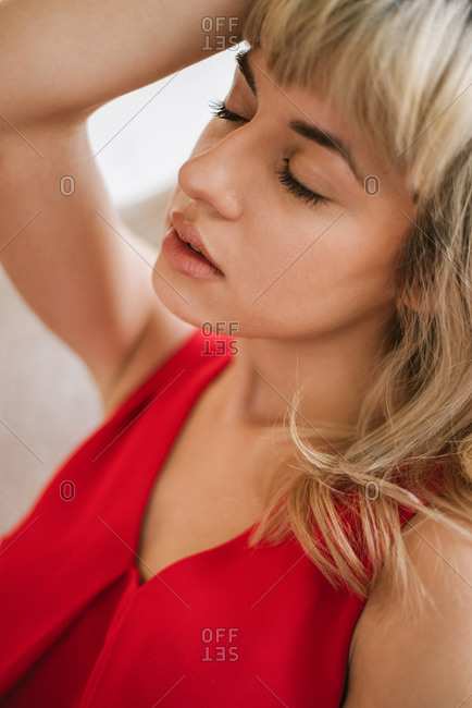Portrait of beautiful blond young woman wearing red dress