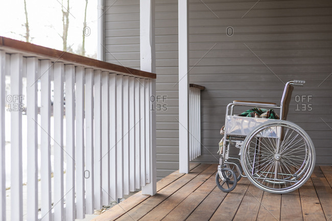Empty wheelchair and blanket on porch