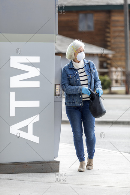 Woman wearing gloves and mask to prevent coronavirus transmission at ATM machine