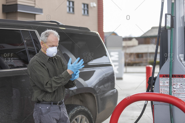 Man wearing surgical gloves and mask at gas station