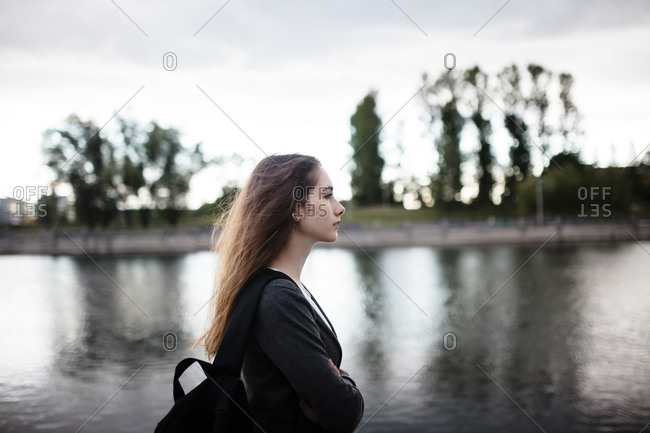 Woman walking near lake in cloudy weather
