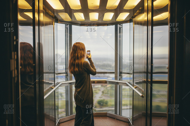 Belarus, Minsk, Woman standing in transparent elevator