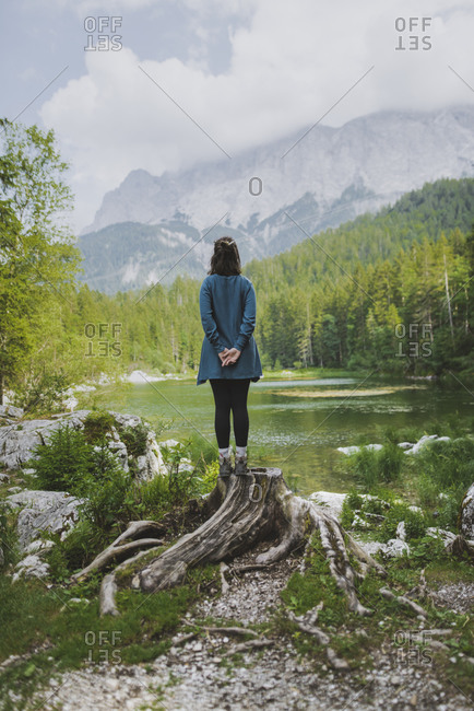 Germany, Bavaria, Eibsee, Young woman standing on stump by Frillensee lake in Bavarian Alps