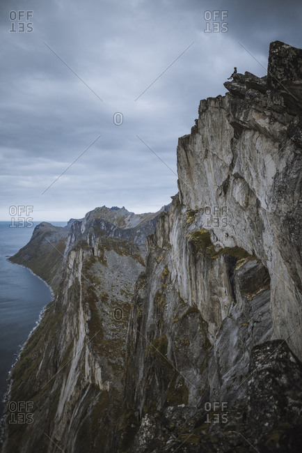 Norway, Senja, Man sitting on the edge of steep cliff on top of Segla mountain
