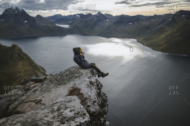 Norway, Senja, Man taking photo sitting on edge of steep cliff on top of mountain Segla